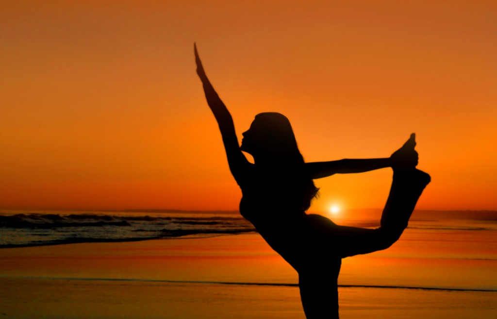 Healthy young woman practicing yoga at sunset on the beach